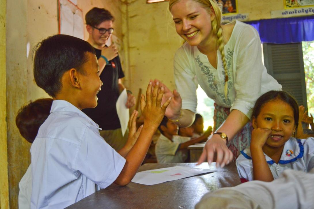 A high school volunteer plays a game with a young boy during her class in Cambodia